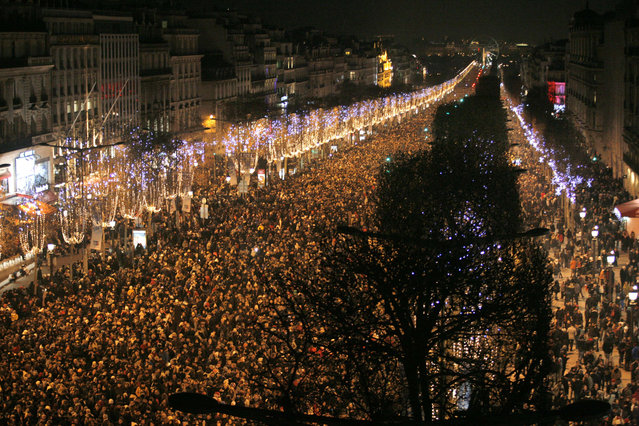 People gather on the Champs-Elysees avenue in Paris before celebrating the New Year on December 31, 2014. (Photo by Matthieu Alexandre/AFP Photo)