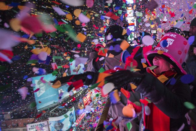 Revellers toss confetti over Times Square from a hotel balcony as the clock strikes midnight during New Year's Eve celebrations in New York January 1, 2015. (Photo by Keith Bedford/Reuters)