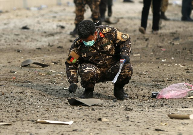 An Afghan security personnel investigates the site of a suicide attack in Kabul January 5, 2015. (Photo by Omar Sobhani/Reuters)