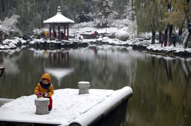 A boy plays with snow in a park in central Beijing, China, November 22, 2015. (Photo by Jason Lee/Reuters)