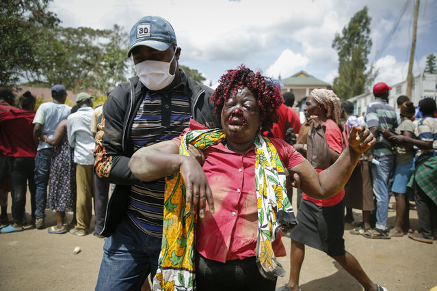 A woman who was injured after being trampled is helped away, after residents desperate for a planned distribution of food for those suffering under Kenya's coronavirus-related movement restrictions pushed through a gate and created a stampede, causing police to fire tear gas and leaving several injured, at a district office in the Kibera slum, or informal settlement, of Nairobi, Friday, April 10, 2020. (Photo by Brian Inganga/AP Photo)