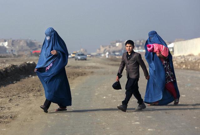 Afghan women and a boy make their way in Kabul, Afghanistan, Sunday, November 15, 2015. (Photo by Rahmat Gul/AP Photo)