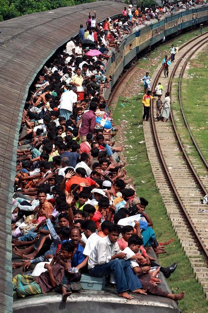 Muslim passengers sit on top of a crowded train in Dhaka, Bangladesh. Hundreds of Bangladeshi Muslims are heading home to celebrate Eid al-Fitr, a Muslim feast marking the end of the holy fasting month of Ramadan. (Photo by Pavel Rahman/Associated Press)