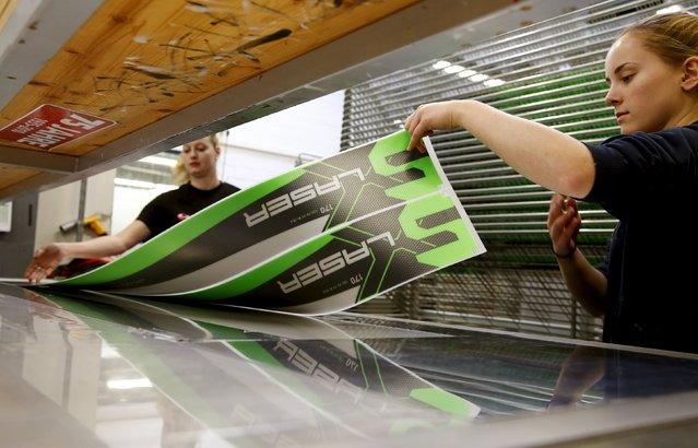 Employees take out the top layer of a ski out of a screen printing machine at the plant of Swiss ski manufacturer Stoeckli in Malters, Switzerland November 25, 2015. (Photo by Arnd Wiegmann/Reuters)