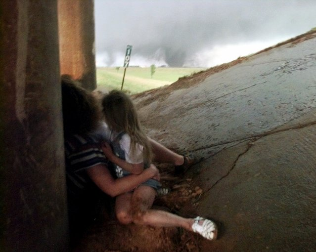 Tammy Holmgren huddles beneath a highway underpass with her two daughters, Megan, 6, right, and Katlyn, 2, partially obscured, as a tornado approaches along the H.E. Bailey Turnpike outside Newcastle, Okla., Monday, May 3, 1999. The family was uninjured, but the tornado left a trail of death and destruction through central Oklahoma. (Photo by J. Pat Carter/AP Photo)