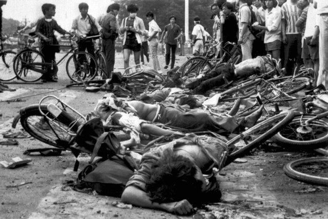 The bodies of dead civilians lie among mangled bicycles near Beijing's Tiananmen Square after pro-democracy student demonstrations sparked a massacre on June 4, 1989. (Photo by AP Photo)