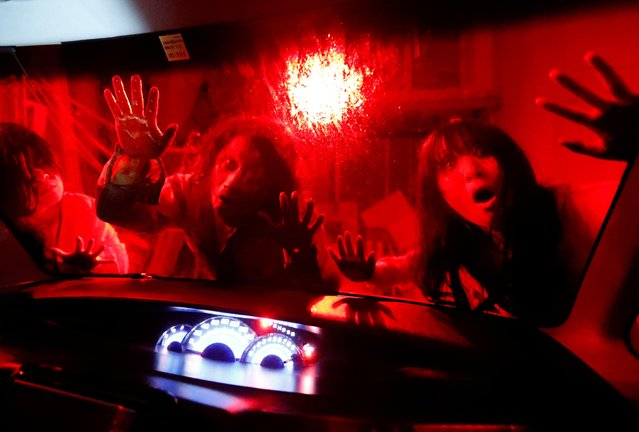Actors dressed as zombies and ghouls perform during a drive-in haunted house show by Kowagarasetai (Scare Squad), for people inside a car in order to maintain social distancing amid the spread of coronavirus, at a garage in Tokyo, Japan on July 3, 2020. (Photo by Issei Kato/Reuters)