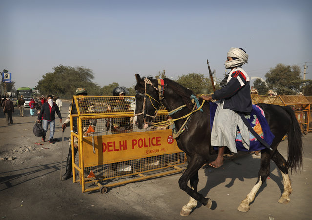 A Nihang or a Sikh warrior on a horse arrives at Singhu, Delhi-Haryana border for ongoing farmers protest against three farm bills, in New Delhi, India, Wednesday, January 27, 2021. Tens of thousands of farmers who stormed the historic Red Fort on India's Republic Day are again camped outside the capital after the most volatile day of their two-month standoff left one protester dead and more than 300 police officers injured. (Photo by Manish Swarup/AP Photo)