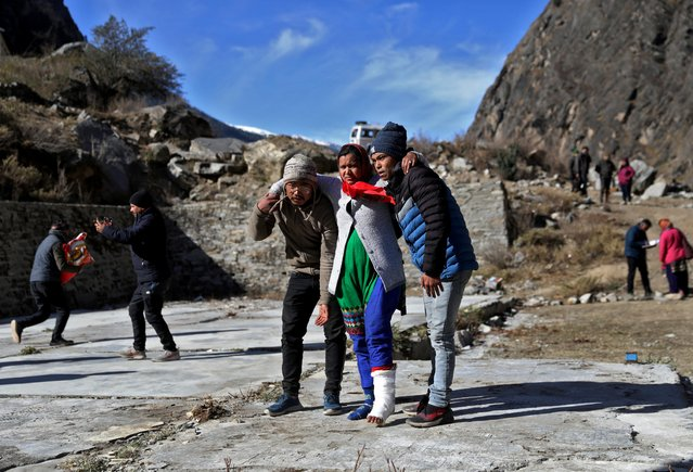People help an injured woman to board a helicopter after a flash flood swept a mountain valley destroying dams and bridges, at Lata village in Chamoli district, in the northern state of Uttarakhand, India, February 12, 2021. (Photo by Anushree Fadnavis/Reuters)
