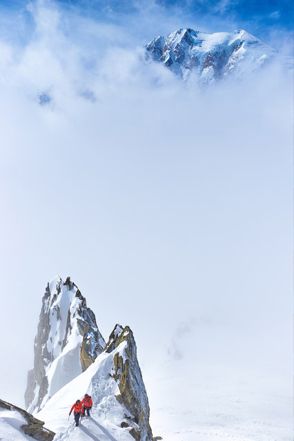 """""""Mont Blanc – the Queen of the Alps"""". The south face of Mont Blanc is counted among the top 10 most dangerous climbs in Europe. On the photograph, dramatic clouds reveal the very summit of Mont Blanc with its numerous ice seracs. In the bottom part of the photograph we can see a pair of mountaineers traversing the ridge of Aiguille Marbrees, above the town of Courmayeur, Aosta, Italy. (Photo and caption by Kamil Tamiola/National Geographic Traveler Photo Contest)"""