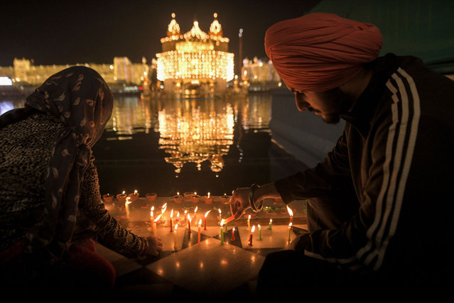 Sikh devotees light candles on the eve of the birth anniversary of the fourth Sikh Guru Ramdas, at the illuminated Golden Temple in Amritsar on November 1, 2020. (Photo by Narinder Nanu/AFP Photo)
