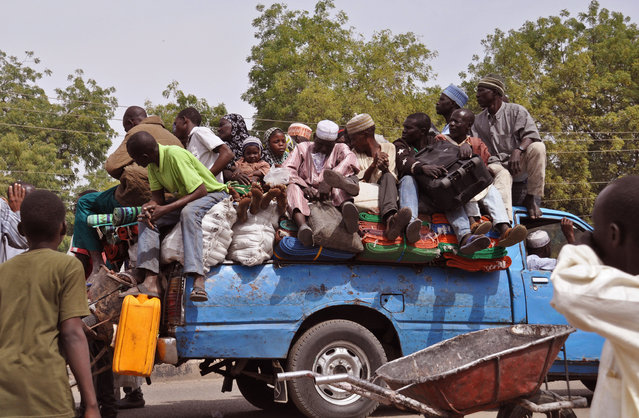 In this photo taken Tuesday, January 27, 2015, villagers sit on the back of a small truck as they and others flee the recent violence near the city of  Maiduguri, Nigeria.  Islamic extremists are rampaging through villages in northeast Nigeria's Adamawa state, killing, burning and looting with no troops deployed to protect civilians, fleeing villagers said Wednesday. (Photo by Jossy Ola/AP Photo)
