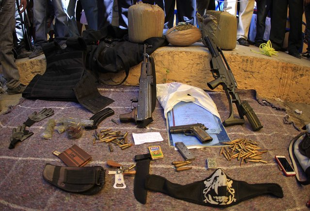 Weapons, ammunition and bags of marijuana (top), which were seized during separate operations by members of the Community Police of the FUSDEG (United Front for the Security and Development of the State of Guerrero), are put on display during a presentation in the village of Petaquillas, on the outskirts of Chilpancingo, in the Mexican state of Guerrero, February 1, 2015. (Photo by Jorge Dan Lopez/Reuters)