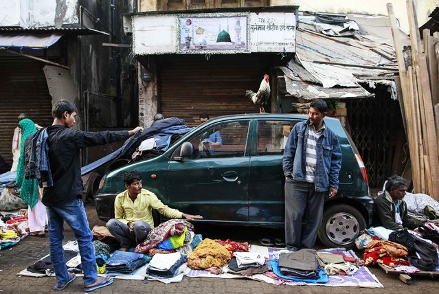 A rooster stands on a car as vendors sell clothes on the roadside at a second-hand street side clothing market in Mumbai January 28, 2015. The market is open daily for three hours and hundreds of vendors gather to barter or sell used clothing. (Photo by Danish Siddiqui/Reuters)