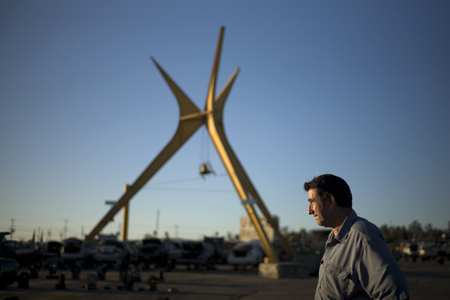 In this Wednesday, November 11, 2015 photo, owner Nick Adlen pauses for photos near the 1950s googie-styled arches at Aadlen Brothers Auto Wrecking, also known as U Pick Parts, in the Sun Valley section of Los Angeles. (Photo by Jae C. Hong/AP Photo)