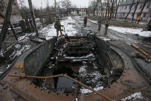 Members of the armed forces of the separatist self-proclaimed Donetsk People's Republic gather near a burnt armoured vehicle in Vuhlehirsk, Donetsk region, February 4, 2015. (Photo by Maxim Shemetov/Reuters)