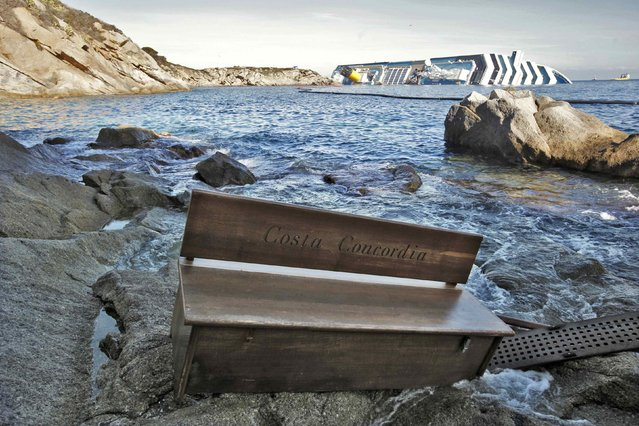 A bench engraved with the name of the grounded Costa Concordia cruise ship (seen at rear) is seen washed up on the shore of Giglio island, in this January 20, 2012 file photo. (Photo by Paul Hanna/Reuters)
