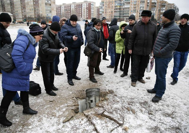 People look at the remains of a rocket shell on a street in the town of Kramatorsk, eastern Ukraine February 10, 2015. Three people were killed and 15 wounded in the rocket strike on the town of Kramatorsk on Tuesday, the government-controlled regional administration said in a statement. (Photo by Gleb Garanich/Reuters)
