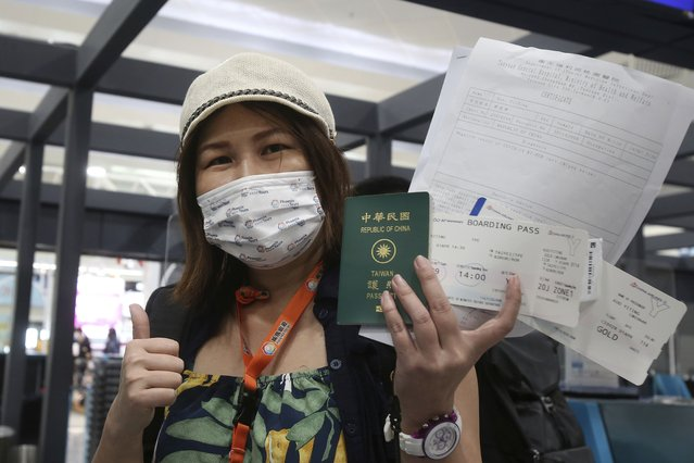 Taiwanese traveler Kuo Yitting of the first group of Palau-Taiwan Travel Corridor shows her boarding pass and a report of virus antigen test before leaving Taiwan, at Taoyuan International Airport in Taoyuan, northern Taiwan, Thursday, April 1, 2021. The Palau-Taiwan Travel Corridor, allowing people to travel between the islands without a COVID-19 quarantine, has started Thursday. (Photo by Chiang Ying-ying/AP Photo)