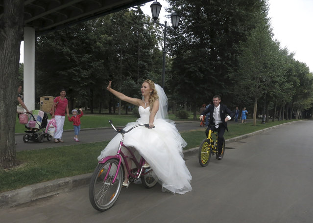 Yelena Babkini (L) and her husband wave as they ride through Gorky Park on bicycles after having been married earlier in the day in Moscow, August 15, 2013. (Photo by Gary Hershorn/Reuters)