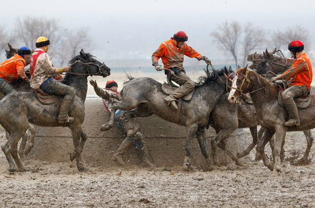 Kyrgyz riders take part in a Kok-Boru regional competition in the village of Sokuluk in Chui Region, Kyrgyzstan March 30, 2021. Kok-Boru is a traditional Central Asian game similar to polo, in which horsemen try to drop the headless carcass of a goat in an opponent's goal. (Photo by Vladimir Pirogov/Reuters)