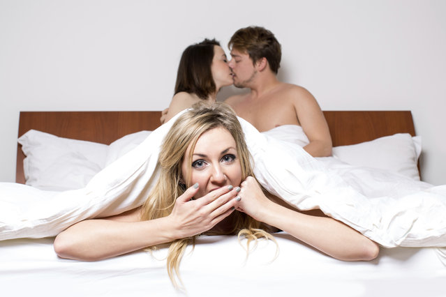 Cheeky young woman having a threesome in bed. (Photo by FantasticRabbit/Getty Images/iStockphoto)