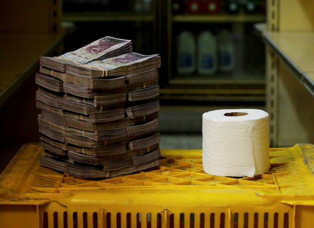A toilet paper roll is pictured next to 2,600,000 bolivars, its price and the equivalent of 0.40 USD, at a mini-market in Caracas, Venezuela August 16, 2018. It was the going price at an informal market in the low-income neighborhood of Catia. (Photo by Carlos Garcia Rawlins/Reuters)