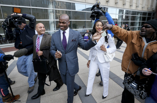 Adrian Peterson and his wife Ashley gret fans outside the federal court house, Friday, February 6, 2015 in Minneapolis. The NFL Players Association's attempt to have Minnesota Vikings running back Adrian Peterson reinstated has been taken under advisement by a federal judge. U.S. District Judge David Doty heard arguments from the NFLPA and the NFL on Friday. (Photo by Brian Peterson/AP Photo/Star Tribune)