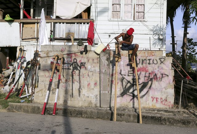 A member of the Kaisokha Moko Jumbies straps on his stilts while sitting on a wall of the San Fernando based cultural group in Trinidad on February 9, 2015. (Photo by Andrea De Silva/Reuters)