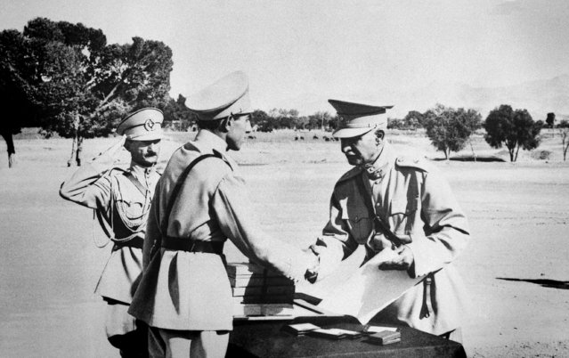 """In this August 19, 1941 file photo, Reza Shah Pahlavi, hands second son, Ali Reza, commission as officer at graduation exercises at Iran's """"West Point"""" in Tehran, Iran prior to Anglo-Russian action. The discovery in Iran of a mummified body near the site of a former royal mausoleum has raised speculation it could be the remains of the late Reza Shah Pahlavi, founder of the Pahlavi dynasty. (Photo by AP Photo)"""