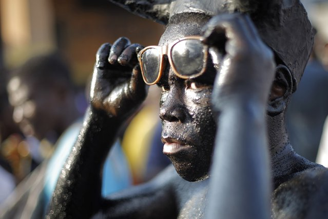 A reveller holds his glasses as he takes part in the National Carnival 2015 annual parade in Port-au-Prince February 15, 2015. (Photo by Andres Martinez Casares/Reuters)
