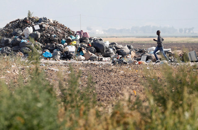 "An African migrant laborer runs near a heap of garbage outside the camp known as the ""Great Ghetto"" near Foggia, Italy on August 8, 2018. The camp was bulldozed by the authorities following a fire that killed three migrants. But with accommodation at a premium, the ghetto has risen again from the rubble - a shanty town of tiny shacks made of corrugated iron and wooden planks. Home to up to 1,000 people, it has zero amenities. Other migrants live in an official, albeit overcrowded and decrepit refuge, which has running water and electricity. It was set up last year after the Great Ghetto was bulldozed. (Photo by Alessandro Bianchi/Reuters)"