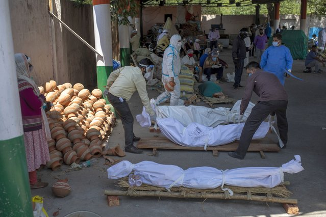 People line up dead bodies of those who died of COVID-19 at a crematorium, in New Delhi, India, Saturday, April 24, 2021. (Photo by Altaf Qadri/AP Photo)