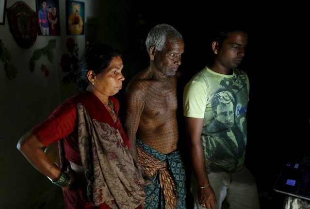 Mahettar Ram Tandon, 76, (C), a follower of Ramnami Samaj, who has tattooed the name of the Hindu god Ram on his full body, watches a religious movie on a computer with his wife and son (R) inside his house in the village of Jamgahan, in the eastern state of Chhattisgarh, India, November 17, 2015. �It was my new birth the day I started having the tattoos�, Tandon said. �The old me had died�. (Photo by Adnan Abidi/Reuters)