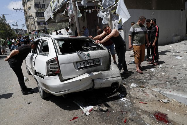 Residents inspect a car that was hit in an Israeli airstrike that killed three people in the car, on the main road in Gaza City, Wednesday, May 12, 2021. (Photo by Adel Hana/AP Photo)