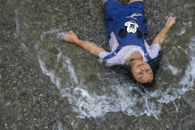 A girl plays in a flooded street at Srimahaphot district in Prachin Buri September 29, 2013. More than 2 million people have been affected by flooding in Thailand, officials said on Monday, while authorities warned that more heavy rains could inundate the country's northeast but offered assurances that there would be no repeat of 2011 when floodwaters reached central industrial areas and near Bangkok. (Photo by Athit Perawongmetha/Reuters)