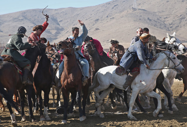 Teammates of Afghan horse riders celebrate their victory during a friendly buzkashi match on the outskirts of Kabul, Afghanistan, Thursday, January 15, 2015. (Photo by Massoud Hossaini/AP Photo)