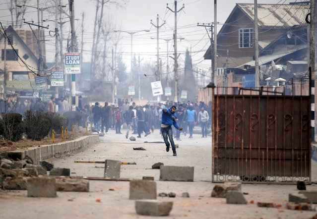 A Kashmiri protester throws a stone towards Indian police during a protest in Srinagar, January 14, 2016. Hundreds of demonstrators on Thursday protested on the Srinagar airport road after the body of a missing youth was found near a railway track, local media reported. (Photo by Danish Ismail/Reuters)