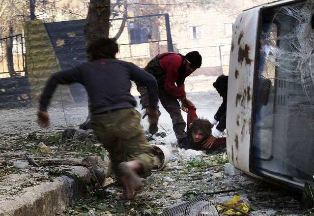 """Free Syrian Army"" fighters rush to help their fellow fighter after he was shot by a sniper loyal to Syria's President Bashar al-Assad in Aleppo's Salaheddine neighborhood, on Oktober 9, 2013. (Photo by Ammar Abdullah/Reuters)"