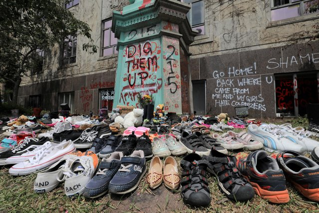 Children's shoes line the base of the defaced Ryerson University statue of Egerton Ryerson, considered an architect of Canada's residential indigenous school system, following the discovery of the remains of 215 children on the site of British Columbia's former Kamloops Indian Residential School, in Toronto, Ontario, Canada on June 2, 2021. (Photo by Chris Helgren/Reuters)