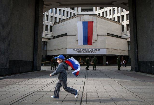 In this Wednesday, March 26, 2014 file photo a boy runs with a Russian national flag at the Crimean parliament in Simferopol, Crimea. (Photo by Alexander Polegenko/AP Photo)