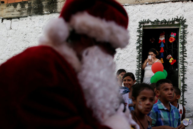 Santa Claus walks during a visit to residents of the slum of Petare in Caracas, Venezuela, December 11, 2016. (Photo by Ueslei Marcelino/Reuters)
