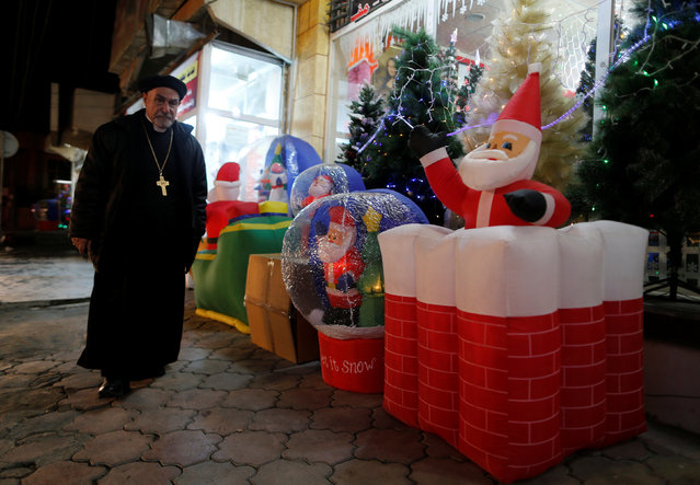 Iraqi priest walks past a market for Christmas decorations in the northern Iraqi city of Erbil, December 23, 2016. (Photo by Ammar Awad/Reuters)