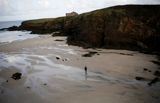 """Santi Diaz Mosquera, 41, a """"percebeiro"""" (barnacle fisherman), walks on Santa Comba beach after collecting barnacles on the coast of Ferrol, in the northwestern Spanish region of Galicia, December 14, 2016. (Photo by Nacho Doce/Reuters)"""