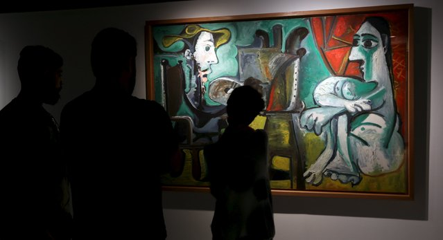 """People stand in front of the painting """"The Paintor and the Model"""" from 1963 by Spanish artist Pablo Picasso at the exhibition """"Picasso and the Spanish modernity"""" at Centro Cultural Banco do Brazil in Sao Paulo March 25, 2015. (Photo by Paulo Whitaker/Reuters)"""