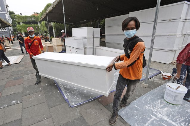 Workers carry a coffin made in anticipation of a surge of COVID-19 cases, at the local government building compound in Surabaya, East Java, Indonesia, Saturday, July 3, 2021. After a slow vaccination rollout, Indonesia is now racing to inoculate as many people as possible as it battles an explosion of cases that have strained hospitals in the country. (Photo by Trisnadi/AP Photo)