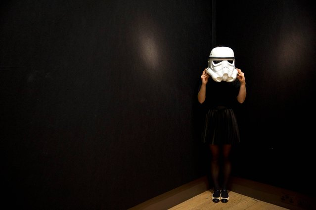 "A Christie's employee poses for photographs with an Imperial Stormtrooper's helmet used as a costume prop in the 1977 movie ""Star Wars: A New Hope"" at premises of the Christie's auction house in London, Thursday, November 28, 2013. The helmet, which is expected to fetch 3,000 to 5,000 pounds ($4,899 to $8,166 or 3,603 to 6,006 euro), features in a ""Pop Culture"" online-only sale that is open for bids until December 5. (Photo by Matt Dunham/AP Photo)"