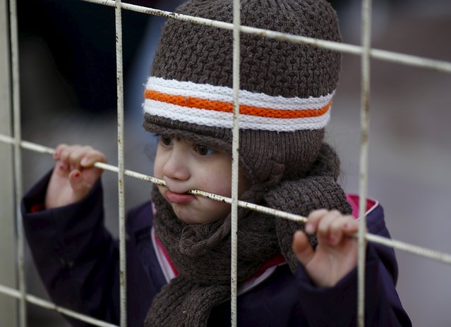 A Syrian boy looks through a gate as others wait to cross into Syria at Oncupinar border crossing in the southeastern city of Kilis, Turkey February 11, 2016.. (Photo by Osman Orsal/Reuters)