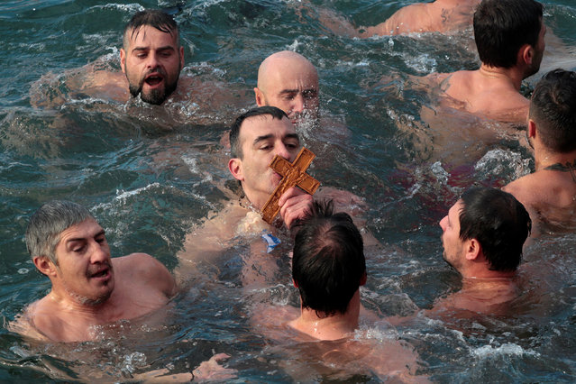 An Orthodox faithful kisses a wooden crucifix during Epiphany day celebrations in Thessaloniki, Greece January 6, 2017. (Photo by Alkis Konstantinidis/Reuters)