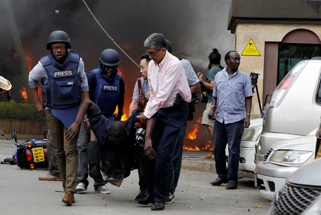 Rescuers and journalists evacuate an injured man from the scene where explosions and gunshots were heard at the Dusit hotel compound, in Nairobi, Kenya on January 15, 2019. (Photo by Njeri Mwangi/Reuters)